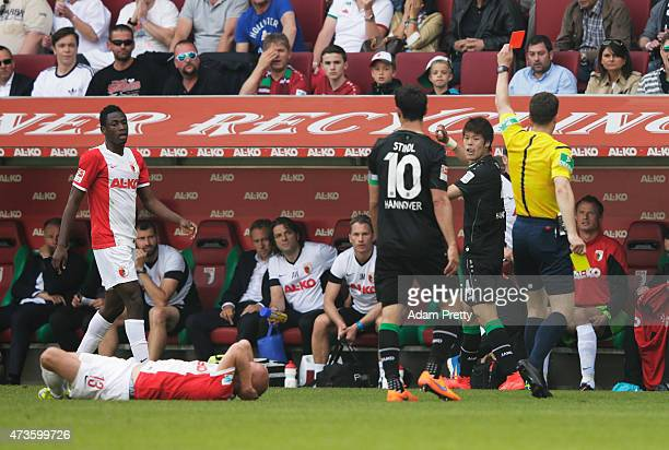 Hiroki Sakai of Hannover 96 is shown a red card during the Bundesliga match between FC Augsburg and Hannover 96 at SGL Arena on May 16, 2015 in...