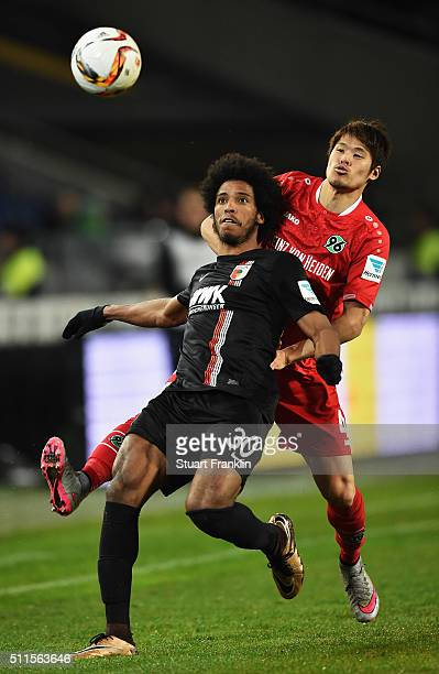 Hiroki Sakai of Hannover is challenged by Caiuby Francisco da Silva of Augsburg during the Bundesliga match between Hannover 96 and FC Augsburg at...