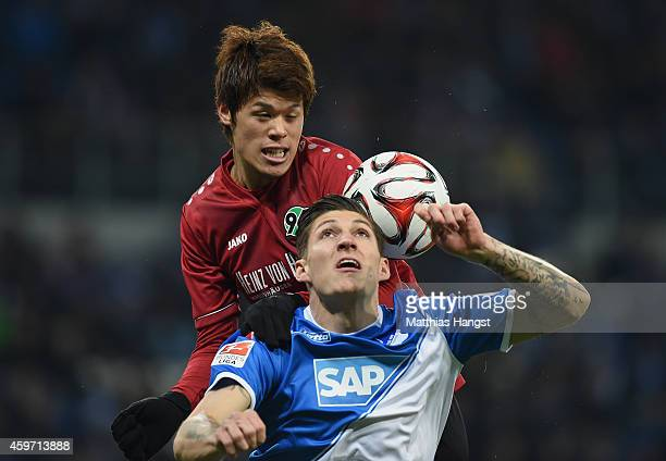 Hiroki Sakai of Hannover jumps for a header with Steven Zuber of Hoffenheim during the Bundesliga match between 1899 Hoffenheim and Hannover 96 at...
