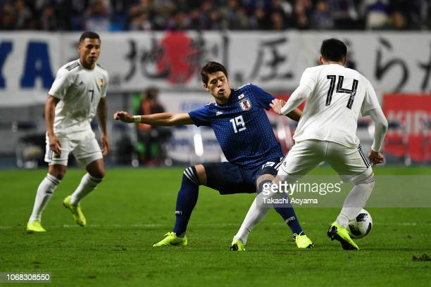 Hiroki Sakai of Japan and Luis Mago of Venezuela compete for the ball during the international friendly match between Japan and Venezuela at Oita...