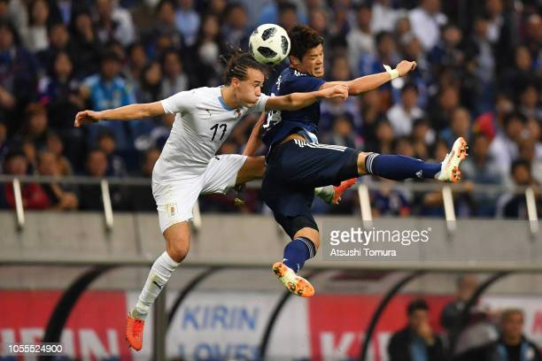 Hiroki Sakai of Japan and Martin Caceres of Uruguay compete for the ball during the international friendly match between Japan and Uruguay at Saitama...