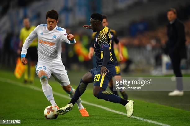 Hiroki Sakai of Olympique Marseille is tackled by Jean-Kevin Augustin of RB Leipzig during the UEFA Europa League quarter final leg two match between...