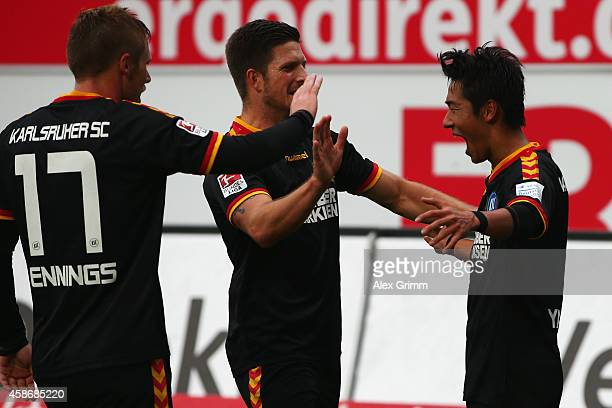 Hiroki Yamada of Karlsruhe celebrates his team's third goal with team mates Dennis Kempe and Rouwen Hennings during the Second Bundesliga match...