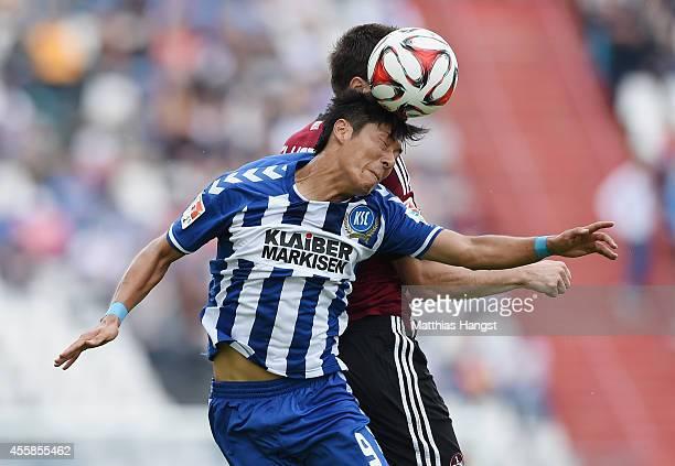 Hiroki Yamada of Karlsruhe jumps for a header with Ondrej Celustka of Nuernberg during the Second Bundesliga match between Karlsruher SC and 1 FC...