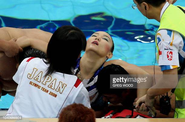 Hiromi Kobayashi from Japan's synchronised swimming team is helped from the water after becoming distressed at the end of the synchronised swimming...