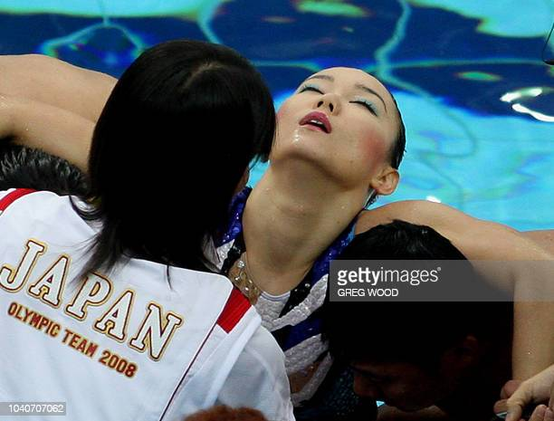 Hiromi Kobayashi from Japan's synchronised swimming team is helped from the water by teammates after becoming distressed at the end of the...
