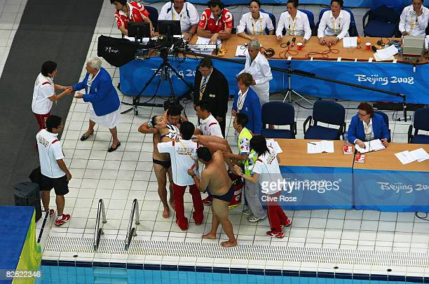 Hiromi Kobayashi of Japan is attended to by medical staff after the Team Event Free Routine Final during the synchronised swimming held at the...