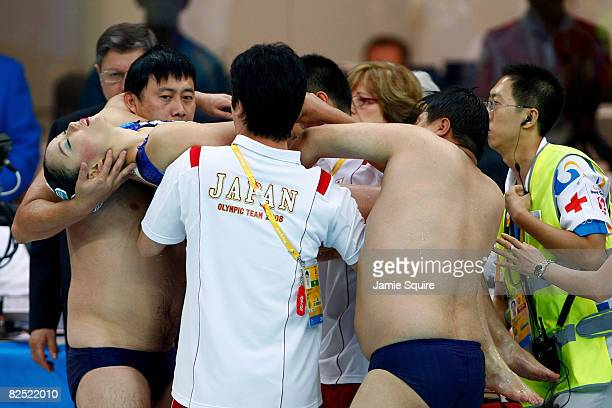 Hiromi Kobayashi of the Japan synchronized swim team is tended to by coaches lifeguards and medical personel after an incident during competition in...