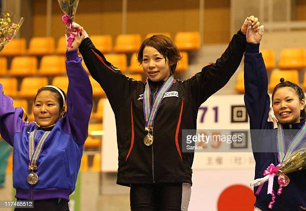 Hiromi Miyake poses for photographs on the podium after winning in the 53kg class during the 25th All Japan Women's Weightlifting Championships at...