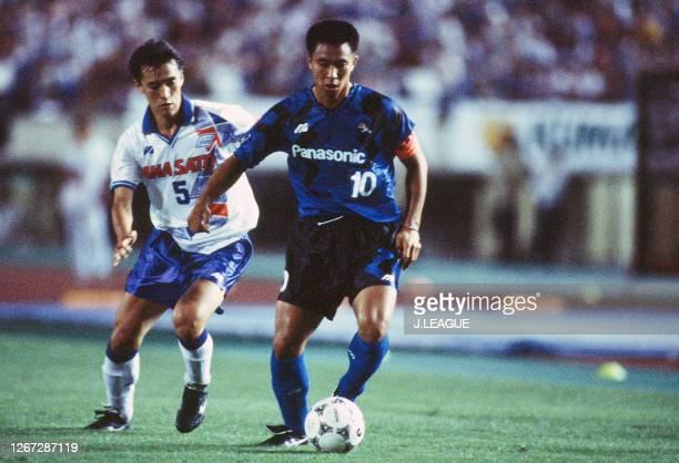 Hiromitsu Isogai of Gamba Osaka controls the ball under pressure of Motohiro Yamaguchi of Yokohama Flugels during the J.League Nicos Series match...