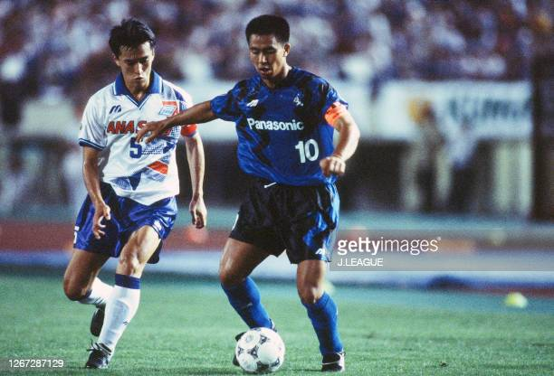 Hiromitsu Isogai of Gamba Osaka controls the ball under pressure of Motohiro Yamaguchi of Yokohama Flugels during the JLeague Nicos Series match...
