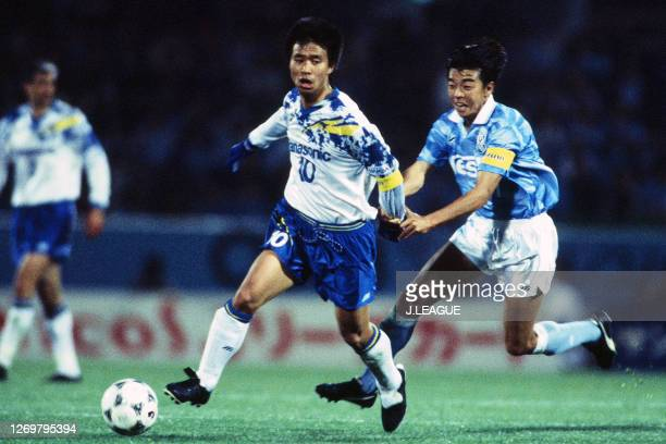 Hiromitsu Isogai of Gamba Osaka controls the ball under pressure of Mitsunori Yoshida of Jubilo Iwata during the J.League Suntory Series match...