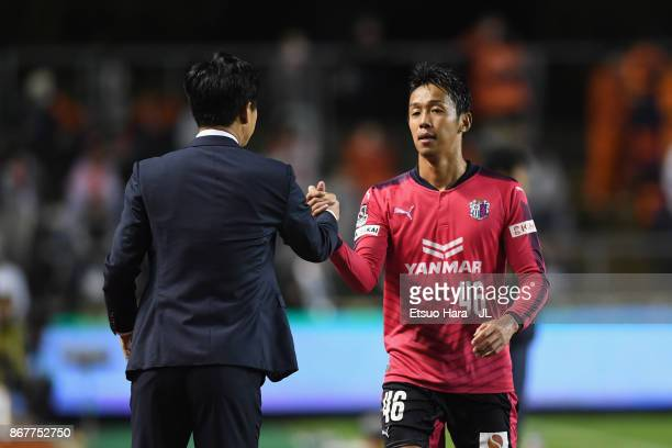 Hiroshi Kiyotake of Cerezo Osaka shakes hands with head coach Yoon Jung Hwan after substituted during the JLeague J1 match between Cerezo Osaka and...