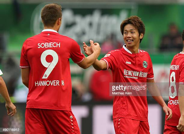 Hiroshi Kiyotake of Hannover jubilates with team mate Artur Sobiech after scoring the second goal during the Bundesliga match between VFL Wolfsburg...