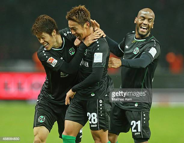 Hiroshi Kiyotake of Hannover jubilates with team mate Hiroki Sakai and Jimmy Briand after scoring the second goal during the Bundesliga match between...