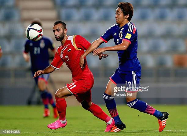 Hiroshi Kiyotake of Japan battles for the ball with Osama Omari of Syriaduring the 2018 FIFA World Cup Asian Group E qualifying match between Syria...