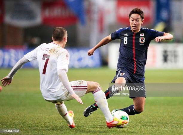 Hiroshi Kiyotake of Japan is tackled during the international friendly match between Japan and Latvia at Home's Stadium Kobe on February 6 2013 in...
