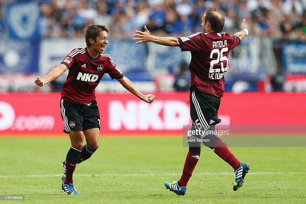 Hiroshi Kiyotake (L) of Nuernberg celebrates his team's second goal with team mate Javier Pinola during the Bundesliga match between 1. FC Nuernberg and Hertha BSC Berlin at Grundig Stadium on August 18, 2013 in Nuremberg, Germany.