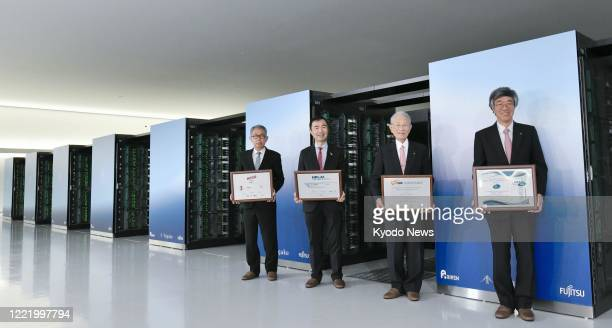 Hiroshi Matsumoto , president of Japan's state-backed Riken research institute, poses for a photo in front of new supercomputer Fugaku in Kobe on...