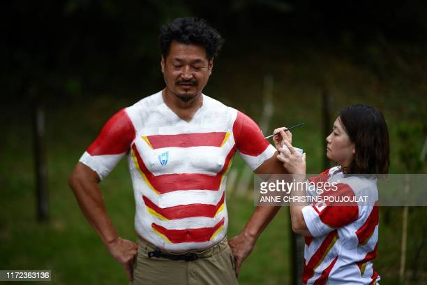 Hiroshi Moriyama has his upper body painted by his wife Rika in the color of the Japanese team in front of the Ecopa Stadium in Shizuoka on September...