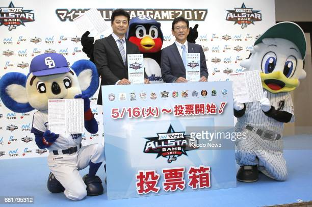 Hiroshima Carp manager Koichi Ogata and Nippon Ham Fighters manager Hideki Kuriyama pose for a photo with mascots in Tokyo on May 11 as they urged...