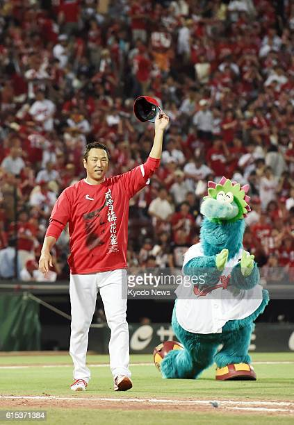 Hiroshima Carp pitcher Hiroki Kuroda acknowledges fans after winning his 200th career game in topflight pro baseball in Japan and the United States...