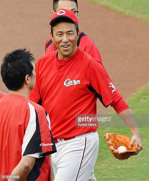 Hiroshima Carp pitcher Hiroki Kuroda smiles after telling teammates before a practice session at Mazda Stadium in Hiroshima on Oct 18 2016 that he...