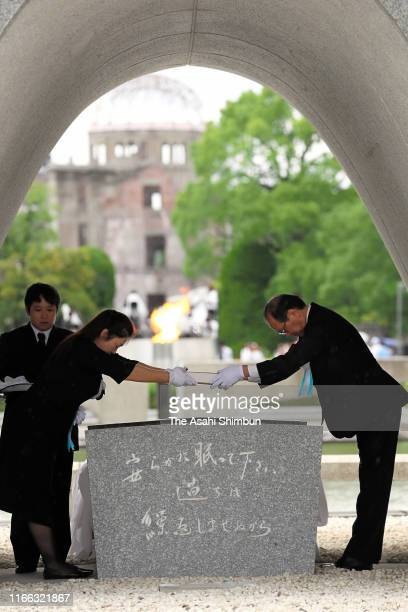 Hiroshima City Mayor Kazumi Matsui receives the namebooks of the victims to dedicate under the cenotaph during the Peace Memorial Ceremony on the...
