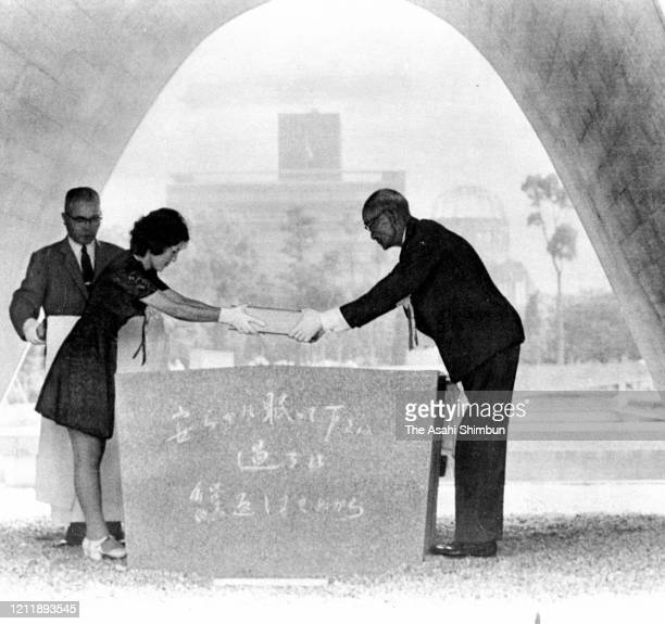 Hiroshima City Mayor Setsuo Yamada receives the victims name books to donate underneath the cenotaph during the Peace Memorial Ceremony on the 28th...