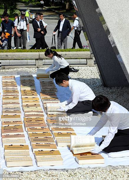 Hiroshima City officers wearing white gloves airs the name books of atomic bombs victims of Hiroshima to check whether there are any damages at...