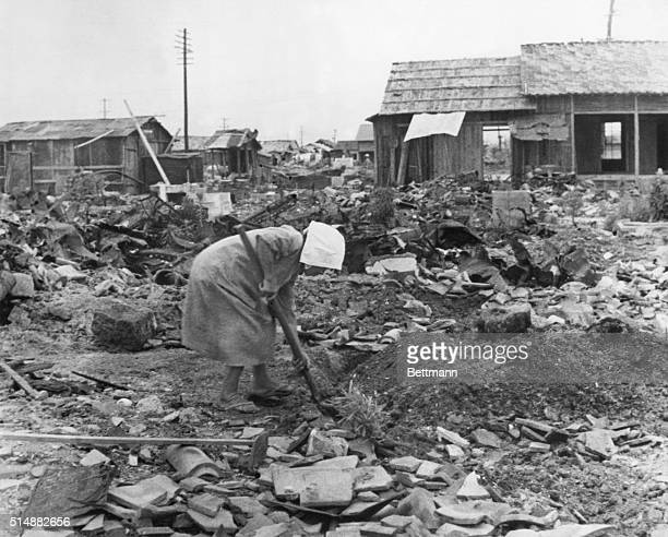 Woman shoveling rubble in ruins of Hiroshima after Atomic explosion Photograph August 1945