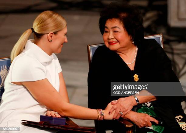 Hiroshima nuclear bombing survivor Setsuko Thurlow touches the hand of Beatrice Fihn leader of ICAN during the award ceremony of the 2017 Nobel Peace...