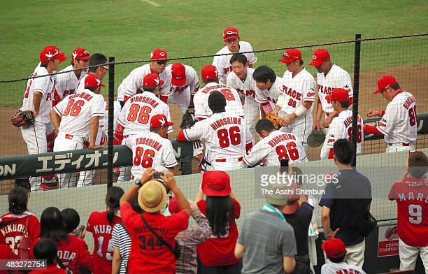 Hiroshima Toyo Carp players wearing special uniform of 'Peace' on the chest and '86' on the back to commemorate August 6 form a huddle during the...
