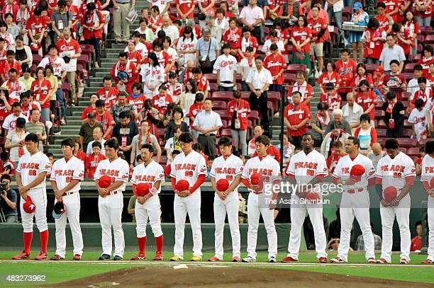 Hiroshima Toyo Carp players wearing special uniforms of 'Peace' on the chest and '86' on the back to commemorate August 6 observe a minute of...