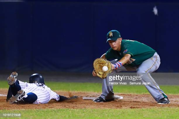 Hirotaka Saito of Japan slides safely into first base against Kyle Weideman of South Africa in the 5th inning during the WBSC U15 World Cup Group B...