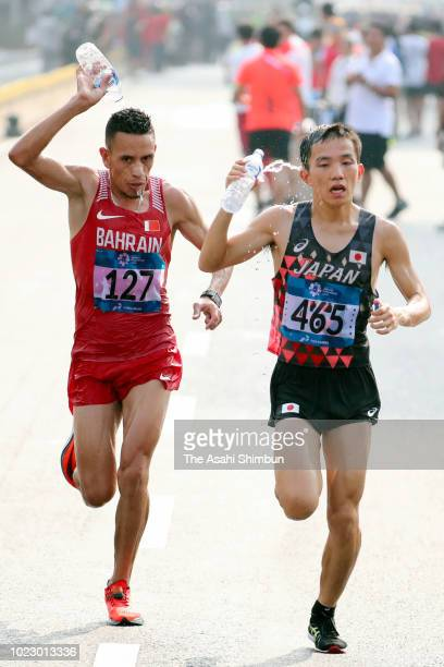 Hiroto Inoue of Japan and Elhassan Elabbassi of Bahrain compete in the Men's Marathon on day seven of the Asian Games on August 25, 2018 in Jakarta,...