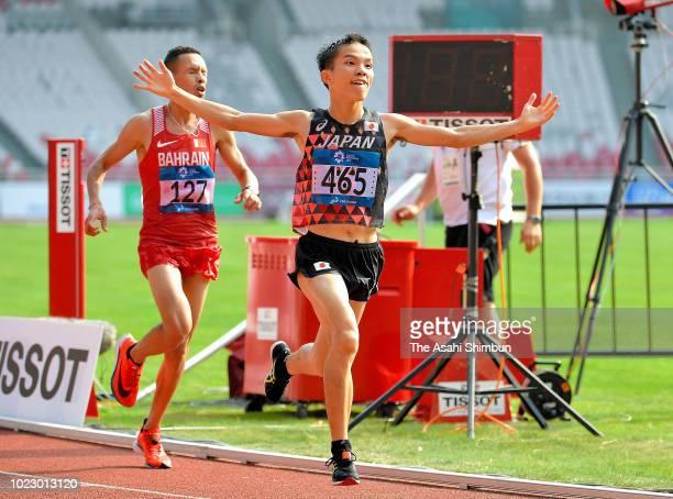 Hiroto Inoue of Japan crosses the finish line to win the Men's Marathon ahead of Elhassan Elabbassi of Bahrain at the GBK Main Stadium on day seven...
