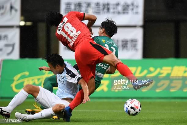 Hiroto Ishikawa of Roasso Kumamoto competes against Atsuya Nodake and Shogo Onishi of Kagoshima United during the J.League Meiji Yasuda J3 match...