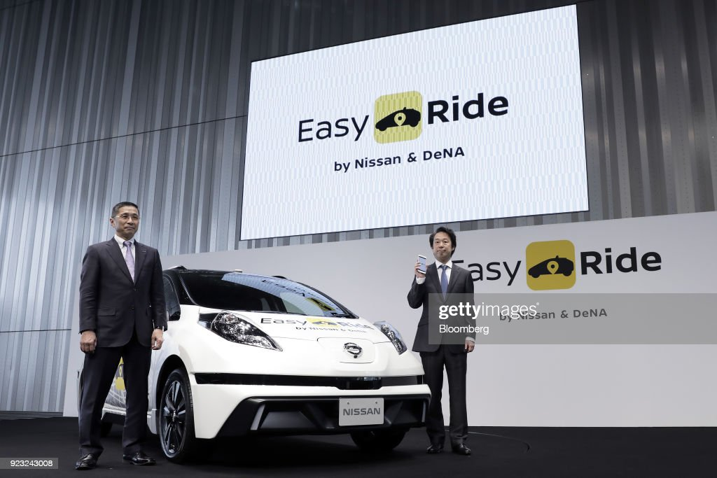 Hiroto Saikawa, president and chief executive officer of Nissan Motor Co., left, and Isao Moriyasu, president and chief executive officer of DeNA Co., pose for a photograph with a Nissan Leaf electric vehicle used for the 'Easy Ride' robot taxi service, jointly developed by Nissan and DeNA, during a news conference in Yokohama, Japan, on Friday, Feb. 23, 2018. The service, which allows the public to use a smartphone app to book 15-minute rides, is scheduled to launch on March 5 for two weeks in Yokohama. Photographer: Kiyoshi Ota/Bloomberg via Getty Images