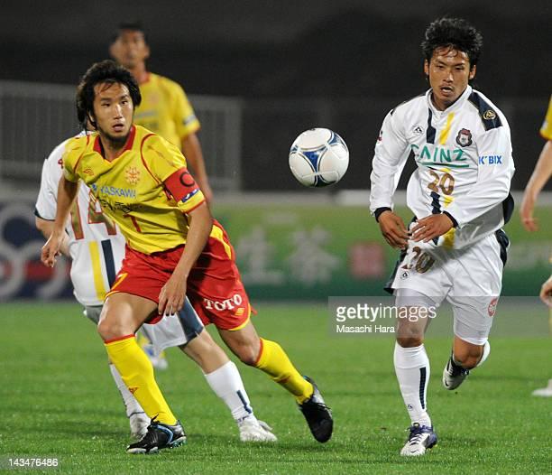 Hiroto Yamamoto of Thespa Kusatsu and Yuji Kimura of Giravanz Kitakyushu compete for the ball during the JLeague Second Division match between Thespa...