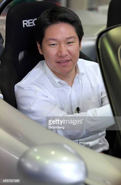 Hiroyasu Koma chief executive officer of GLM Co sits for a photograph in the driver's seat of a Tommykaira ZZ electric vehicle in the company's RD...