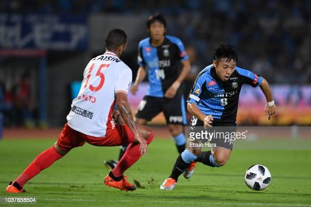 Hiroyuki Abe of Kawasaki Frontale and Eduardo Neto of Nagoya Grampus compete for the ball during the JLeague J1 match between Kawasaki Frontale and...