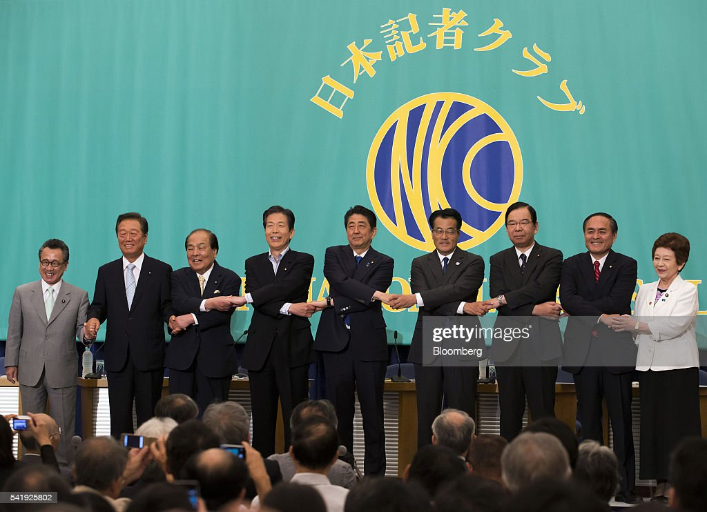Hiroyuki Arai, president of the New Renaissance Party, from left, Ichiro Ozawa, president of the People's Life Party & Taro Yamamoto and Friends, Toranosuke Katayama, co-leader of the Initiatives from Osaka, Natsuo Yamaguchi, chief representative of the New Komeito Party, Shinzo Abe, Japan's prime minister and president of the Liberal Democratic Party (LDP), Katsuya Okada, president of the Democratic Party, Kazuo Shii, chairman of the Japanese Communist Party, Tadatomo Yoshida, president of the Social Democratic Party and Kyoko Nakayama, leader of the Party for Japanese Kokoro, link their hands during a photo session before their debate ahead of the upper house election at the Japan National Press Club in Tokyo, Japan, on Tuesday, June 21, 2016. It is for Bank of Japan to decide what monetary policy methods to use, said Abe during the debate. Photographer: Tomohiro Ohsumi/Bloomberg via Getty Images