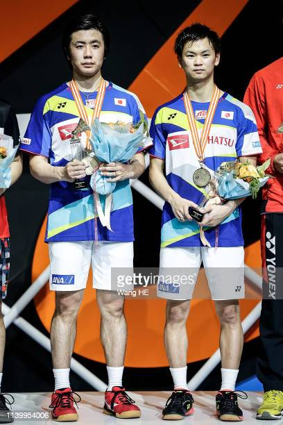 Hiroyuki Endo and Yata Watanabe pose with gold medals on the podium after winning the men's doubles final match against Marcus Ferndldi Gideon and...