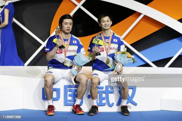 Hiroyuki Endo and Yuta Watanabe of Japan pose on the podium after winning the men's doubles final match at the 2019 Badminton Asia Championships in...