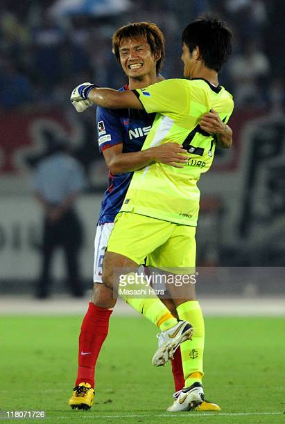 Hiroyuki Taniguchi and goalkeeper Daiki Iikura of of Yokohama F.Marinos celebrate their team's win at the close of the J.League match between...