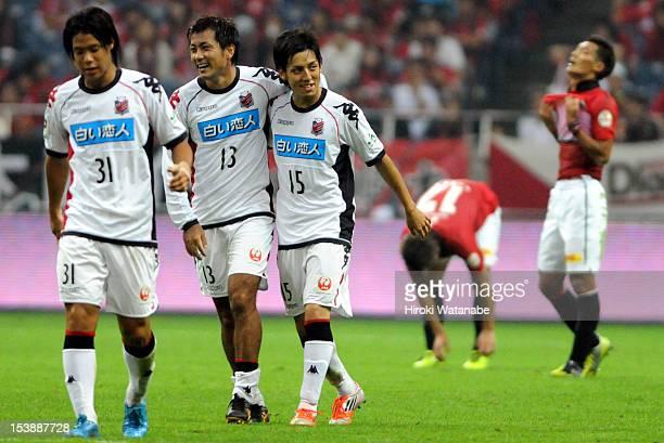 Hiroyuki Yoshida of Consadole Sapporo celebrates a goal with his team mates Yoshihiro Uchimura and Takayuki Mae during the J.League match between...