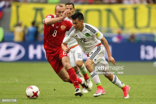 Hirving Lozano of Mexico competes with Denis Glushakov of Russia during the FIFA Confederations Cup Russia 2017 Group A match between Mexico and...