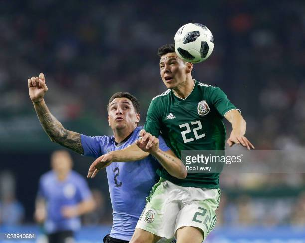 Hirving Lozano of Mexico heads the ball away from Jose Maria Gimenez of Uruguay during the International Friendly match between Mexico and Uruguay at...