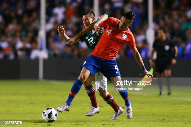 Hirving Lozano of Mexico struggles for the ball against Mauricio Isla of Chile during the international friendly match between Mexico and Chile at La...